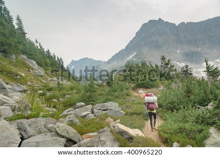 An Asian girl hiking along the Cascade Pass Trail in North Cascade National Park, Washington, USA.  This picture indicates one of the adventure activities in America - stock photo