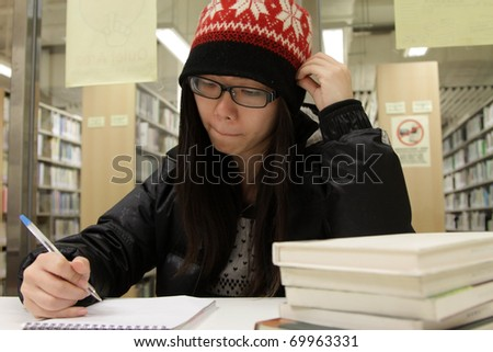 An Asian girl who is reading and studying in library of a University