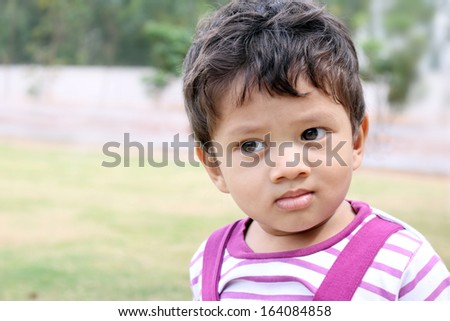 An Asian, Indian baby boy of age 1 Year old in a playground - stock photo