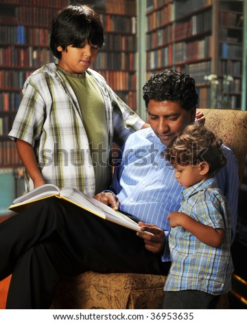 An Asian-Indian dad reading a storybook to his 2-year-old bi-racial son in the home library.  An older son looks on.