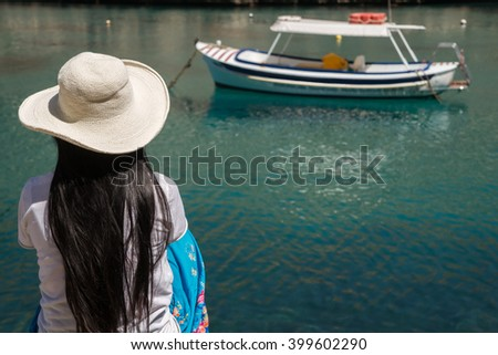 An asian lady with a hat waits for a boat - stock photo
