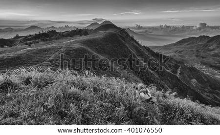 An Asian man crouches  while taking a photo on a mountain in black and white (mono monochrome). - stock photo
