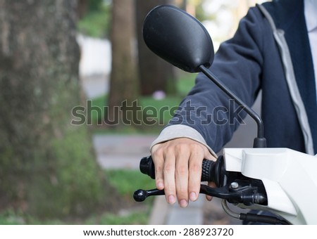 An Asian man driving a scooter in Asia city. - stock photo
