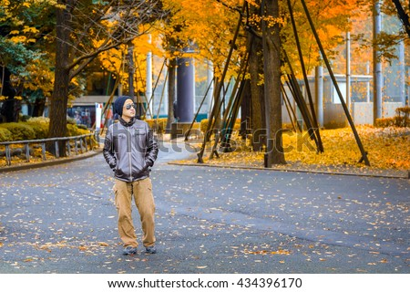 An Asian Man in a Brown Jacket Strolls in a Park in Autumn - stock photo