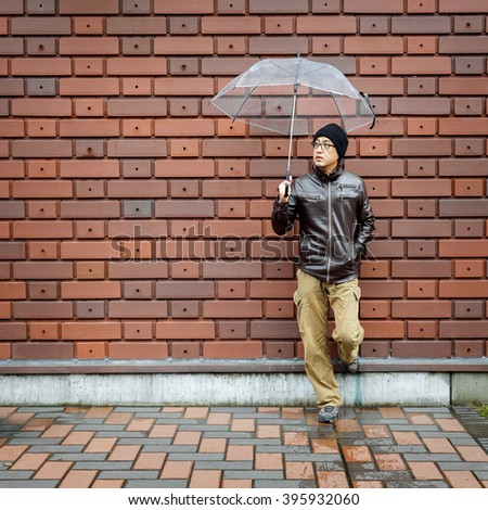 An Asian Man in a Brown Jacket With a Clear Umbrella