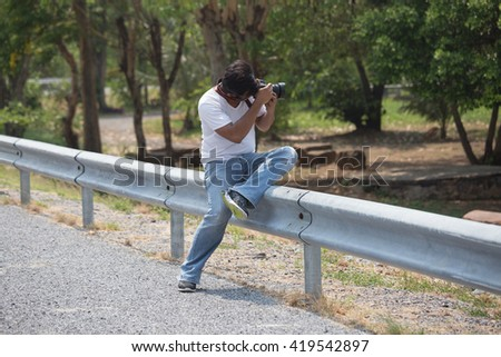 An asian man wears white T-shirt and blue denim sit on steel bar side of road, shooting the landscape with his dslr camera