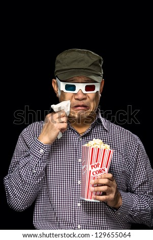 An Asian man weeping during a sad movie. - stock photo