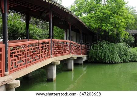 An asian style bridge over green water at Tongli Pearl Pagoda in Wujiang City Jiangsu province China.   - stock photo
