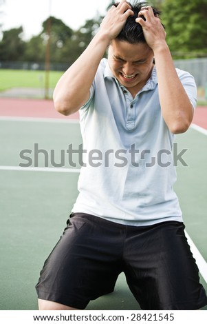 An asian tennis player disappointed in defeat after a tennis match - stock photo