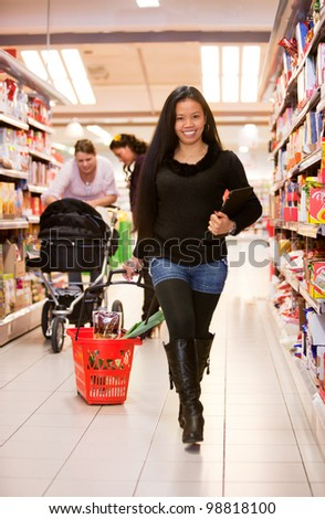 An asian woman in a grocery store with a basket - stock photo