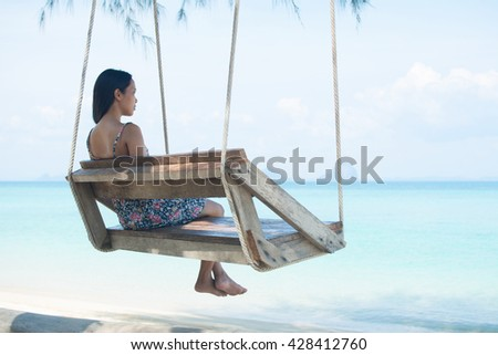 An Asian woman on vacation sits on a rope swing on an idyllic paradise beach and looks out to sea. Travel destinations. - stock photo