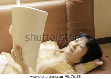 an asian woman relaxing on sofa reading book