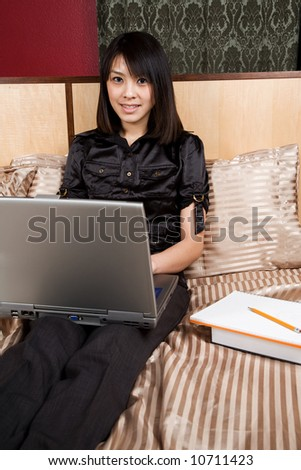 An asian woman working on her laptop on her bed