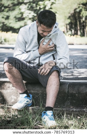 An Asian young man has a heart pain while exercising in a park.