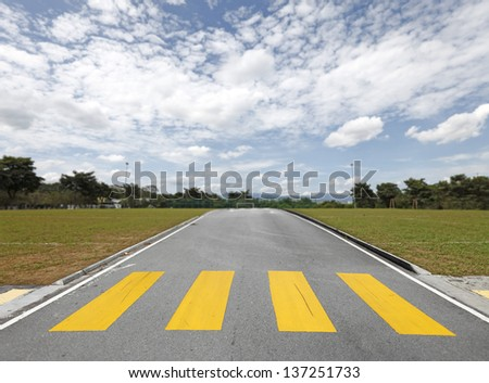 An asphalt road with a yellow zebra crossing on a soccer field leading to the goal mouth on a blue cloudy day.