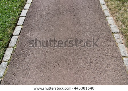 An asphalt walkway in the garden with green grass on both side. one side is green, fresh but the other side is dry and dying