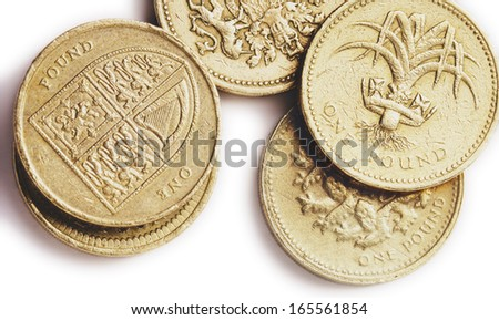 An assortment of British one pound coins, one showing the UK coat of arms, representing the four nations, England, Ireland, Scotland and Wales,another showing a leek, the national plant of Wales. - stock photo