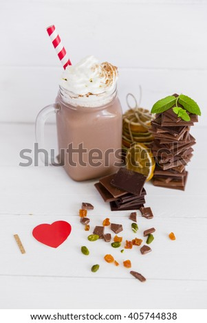 An assortment of dark and milk chocolate with chocolate milkshake and dried fruits on wooden board. I love chocolate concept - stock photo