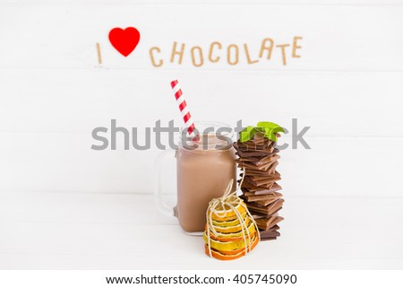 An assortment of dark and milk chocolate with chocolate milkshake and with dried fruits decoration on wooden board. I love chocolate letters - stock photo