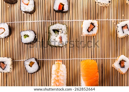 an assortment of different sushi pieces on a wooden bamboo sushi mat - stock photo