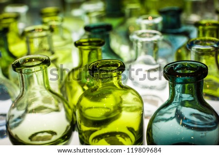 An assortment of empty colorful glass bottles on light box. - stock photo