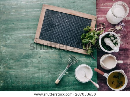 An assortment of fresh herbs and spices on a shabby chic background of colorful wood with a small blank vintage school slate for your menu or recipe, overhead view - stock photo