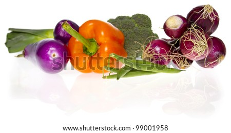 An assortment of fresh vegetables (leek, aubergine, pepper, broccoli, beans, onions) isolated on white.