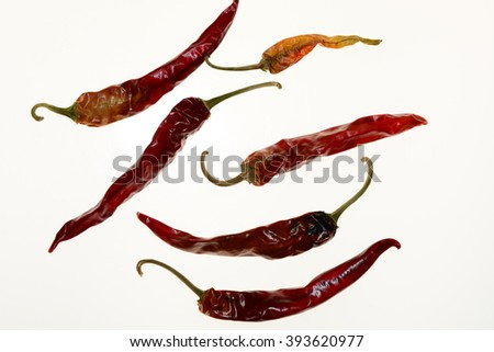 An assortment of hot peppers on a white background.