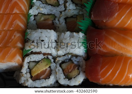 an assortment of japanese sushi on a  rectangular black dinner plate