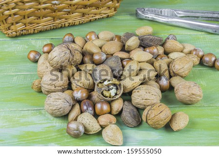 An assortment of nuts on green wooden table - stock photo