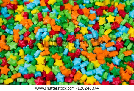 An assortment of shiny, brightly colored hard candy-coated stars which have a plastic look & feel to them fills the entire frame with focus at the center of the image & falling away towards the edges - stock photo