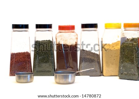 An assortment of spices and measuring cups, isolated on a white background