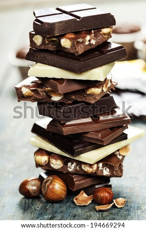 An assortment of  white, dark, and milk chocolate with nuts - on wooden board - stock photo