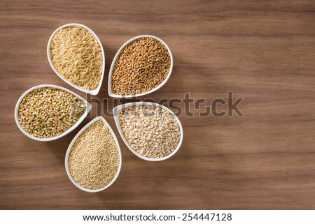 An assortment of whole grains in bowls over a wooden background - stock photo