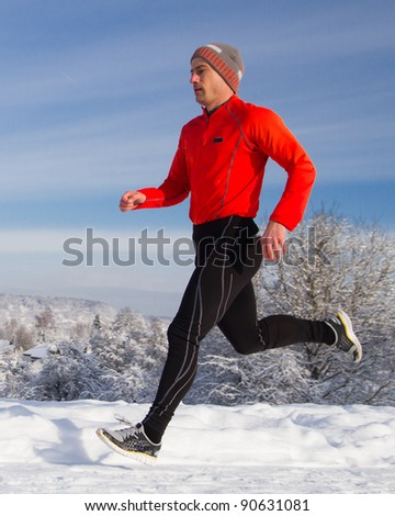 An athlete is jogging in a snowy landscape - stock photo