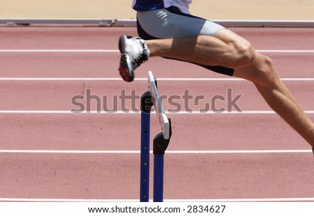An athlete leaping the hurdles