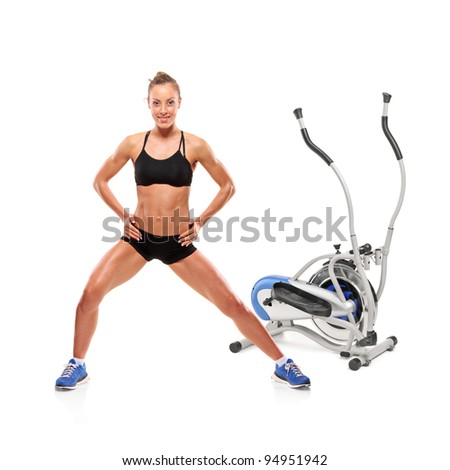 An athlete woman posing in front of a cross trainer machine isolated on white background - stock photo