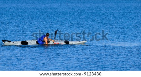 An athletic male kayaker performs float-asisted roll in calm waters of Mission Bay, San Diego, California. Copyspace on top and bottom.