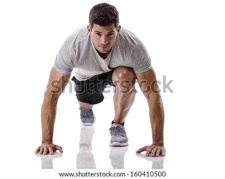 An athletic man ready for start running, isolated over a white background - stock photo