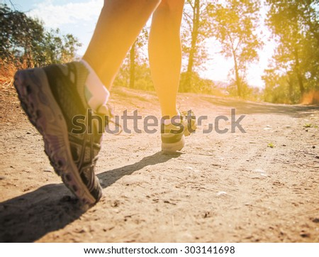 an athletic pair of legs running or jogging on a path during sunrise or sunset toned with a retro vintage instagram filter effect app or action - stock photo