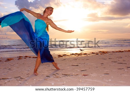 An attractive adult woman is dancing on the beach with the sun behind her and a seagull in the background, she appears to be carefree and happy.