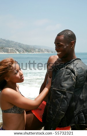 an attractive african american couple enjoy a day at the beach - stock photo
