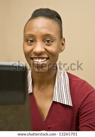 An attractive African American office worker, information  technology specialist or business woman seated at a computer. - stock photo