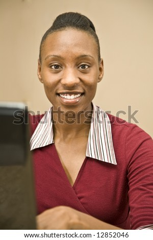 An attractive African American office worker, IT specialist or  business woman seated at a computer. - stock photo