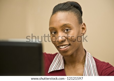 An attractive African American office worker or business  woman seated at a computer. - stock photo