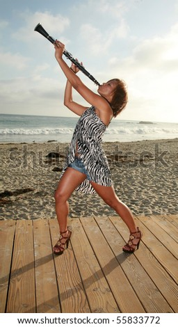 an attractive african american woman plays her clarinet outside at the beach for all to hear and enjoy - stock photo