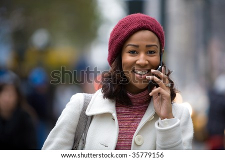 An attractive African American woman talking on her cell phone in the city. - stock photo