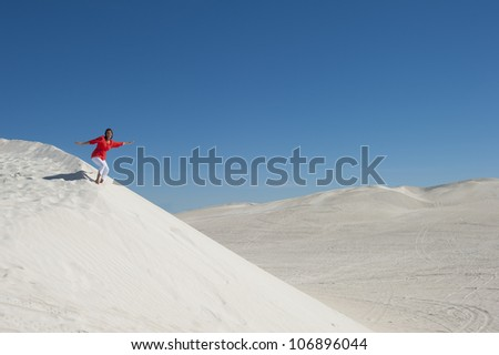 An attractive and confident looking mature woman with red blouse and umbrella, isolated on white sand dune overlooking a desert panorama, with clear blue summer sky as background and copy space.