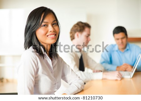 An attractive Asian businesswoman looks at the camera during a meeting with a diverse group of business people including a latino and caucasian male. - stock photo