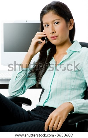 An attractive Asian businesswoman sitting at a desk with computer whilst holding phone